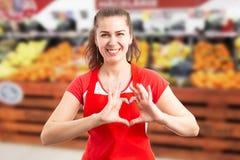 Empregado do supermercado que guarda os dedos como o símbolo do coração imagens de stock