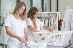 Empregado dois do sexo feminino feliz com cesta de lavanderia imagens de stock royalty free