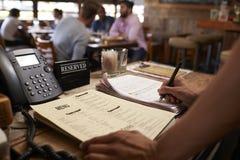 Empregado em um restaurante que escreve para baixo uma reserva da tabela foto de stock
