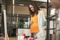 Empregado grávido encantador que vai em licenças de parto Foto de Stock Royalty Free