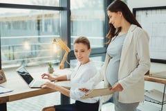 Empregado grávido que dá o original a seu chefe antes que tem suas licenças de parto Foto de Stock Royalty Free