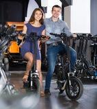 Empregado que ajuda o indivíduo adulto a selecionar a bicicleta na agência alugado Imagem de Stock