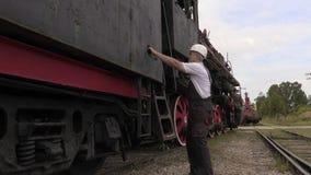 Empregado Railway que fala e que anda perto da locomotiva vídeos de arquivo