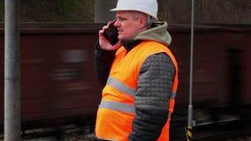 Empregado Railway que fala no telefone celular perto do trem de passagem video estoque
