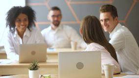 Empregado surpreendido que olha o portátil, compartilhando da boa notícia com os colegas de trabalho