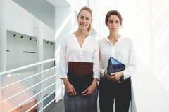 Empregados de mulheres que descansam no interior do escritório após ter incorporado a informação dos originais de papel na almofa Imagem de Stock