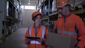 Empregados do armazém em capacetes uniformes e duros que discutem o trabalho que está com a caixa e uma tabuleta nas mãos vídeos de arquivo