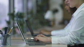 Empregados do sexo feminino que trabalham em computadores no escritório empresarial, email de datilografia vídeos de arquivo