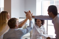 Empregados multirraciais que dão altamente cinco na instrução, mostrando a unidade imagens de stock royalty free