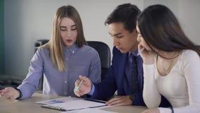 Empregados novos que falam o assento na tabela na empresa do escritório video estoque