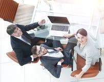 Empregados que sentam-se na mesa e que olham acima Imagens de Stock Royalty Free