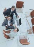 Empregados que sentam-se na mesa e que olham acima Imagem de Stock Royalty Free