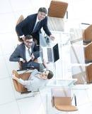 Empregados que sentam-se na mesa e que olham acima Foto de Stock Royalty Free