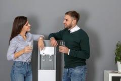 Empregados que têm a ruptura perto do refrigerador de água fotografia de stock royalty free