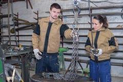 Empregados que usam a maquinaria industrial na fábrica imagens de stock