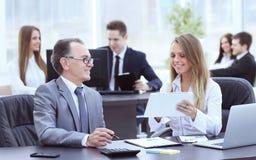 Empregados que usam a tabuleta digital para trabalhar com dados financeiros fotos de stock royalty free