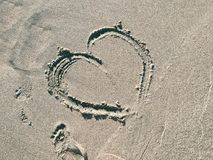 Empreinte de coeur sur le sable d'océan Photographie stock