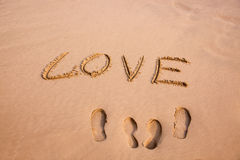 Empreinte de pas et amour écrits dans le sable sur une plage Photographie stock