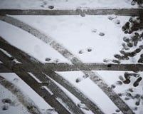 Empreinte de pas et trace de roue de voiture sur l'au sol de neige images libres de droits
