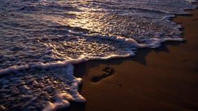 Empreinte de pas sur le sable par l'océan photos libres de droits