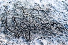"""Empreinte digitale sur le sable sur la côte du lac Victoria """"j'aime l'Ouganda """" image stock"""