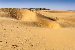 Empreintes de pas d'un touriste de garçon marchant sur des dunes de sable, dunes de SAM de Photo stock