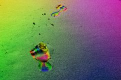 Empreintes de pas dans des couleurs d'arc-en-ciel sur la plage Photographie stock