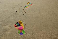 Empreintes de pas dans des couleurs d'arc-en-ciel sur la plage Photographie stock libre de droits