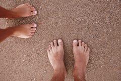 Empreintes de pas dans des couples d'amour dans le sable sur le bord de la mer Photo stock