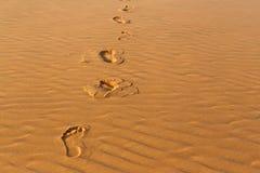 Empreintes de pas humaines du ` s sur le sable onduleux dans le désert Photo libre de droits