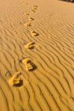 Empreintes de pas humaines du ` s sur le sable onduleux dans le désert Photographie stock libre de droits