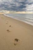 Empreintes de pas sur une plage sablonneuse, nuages orageux foncés Photos stock