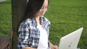 Empresário adulto da mulher de negócio que fala no telefone usando o smartphone e olhando na rede social do computador digital video estoque