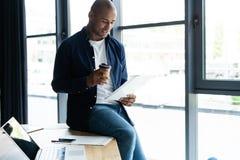 Empresário africano bem sucedido que estuda originais com olhar atento e concentrado, café bebendo no café escuro foto de stock