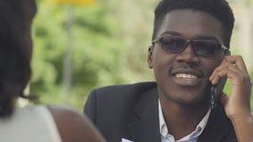 Empresário afro-americano positivo novo no eyewear na moda que tem a conversa telefônica com doação assistente do secretário video estoque