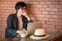 Empresário asiático novo que usa o laptop no café Fotos de Stock
