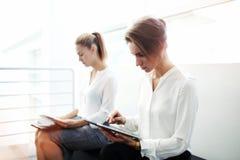 Empresário bem sucedido da mulher que trabalha na almofada de toque quando seu sócio que lê os originais de papel antes da confer Fotos de Stock Royalty Free