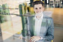 Empresário bem sucedido que sorri na satisfação como verifica a informação em seu laptop ao trabalhar em um escritório domiciliár Imagens de Stock Royalty Free