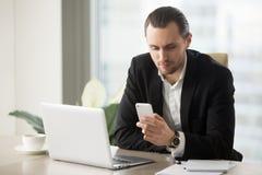 Empresário bem sucedido que usa o app móvel no telefone Imagens de Stock Royalty Free