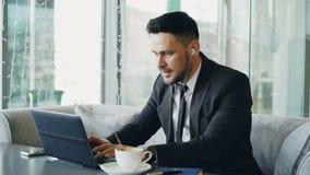 Empresário caucasiano feliz na roupa formal que datilografa em seu portátil ao escutar a música com earbuds em suas orelhas dentr vídeos de arquivo