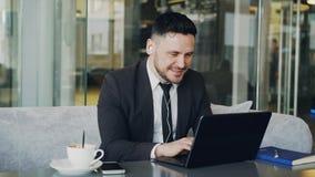 Empresário caucasiano feliz na roupa formal que datilografa em seu portátil ao escutar a música com earbuds em suas orelhas dentr filme