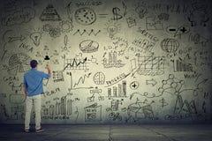 Empresário do homem de negócio que escreve alguns cálculos novos do projeto na parede cinzenta