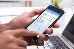 Empresário Doing Online Banking em Smartphone imagem de stock