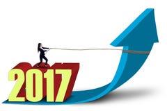 Empresário e números 2017 setas puxando para cima Imagens de Stock Royalty Free