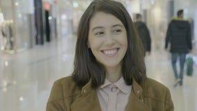 Empresário fêmea angélico feliz que olha lados e que sorri na câmera antes de começar sua compra no centro da alameda - vídeos de arquivo