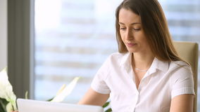 Empresário fêmea bonito no local de trabalho, trabalhando no portátil, café bebendo video estoque
