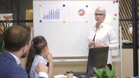 Empresário fêmea que apresenta o stratey financeiro aos colegas multirraciais filme