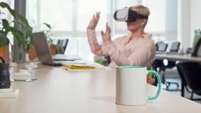 Empresário fêmea que usa óculos de proteção da realidade 3d virtual no escritório video estoque
