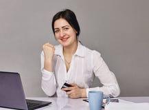 Empresário feliz que trabalha em linha com um portátil no escritório Fotografia de Stock Royalty Free