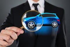 Empres?rio Holding Magnifying Glass em Front Of Blue Car fotos de stock